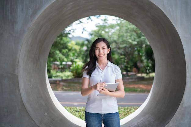 Retrato, sorridente, mulher asiática em uma camisa branca, segurando um laptop.