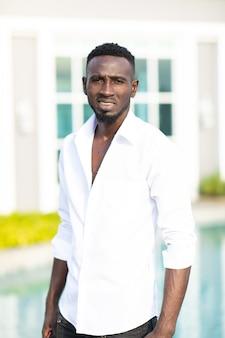 Retrato sorrindo ceo afro-americano jovem empresário em pé à beira da piscina na nova casa. homem bonito homem de pele escura rindo olhar para a câmera.