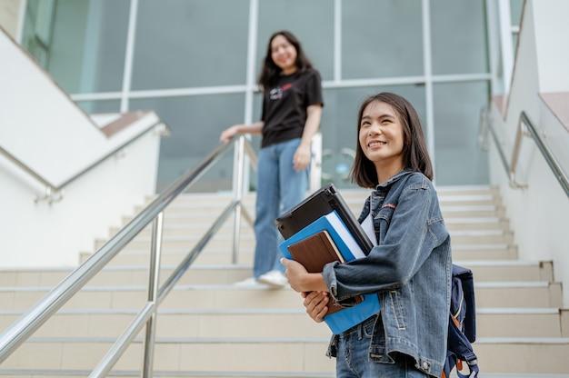 Retrato sorrindo de duas estudantes asiáticas e subindo as escadas adolescente no campo de educação