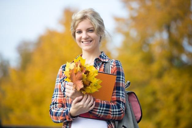 Retrato, sorrindo, jovem, estudante, ao ar livre, segurando, amarela, folhas