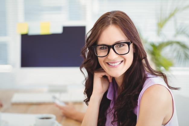 Retrato, sorrindo, mulher, desgastar, óculos, escrivaninha