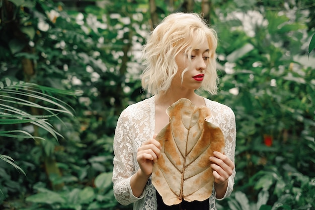Retrato suave de mulher loira no jardim botânico tropical