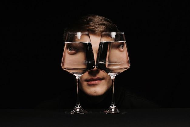 Retrato surreal de um homem estranho olhando através de dois copos d'água