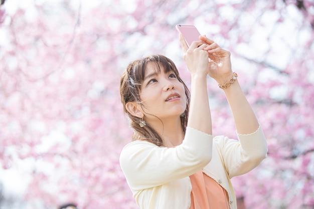 Retrato tirado sob uma árvore de cereja em plena floração