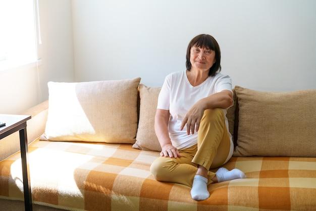 Retrato, tiro na cabeça de uma mulher de meia idade tranquila calma relaxando no aconchegante sofá sozinho em casa bom ha ...