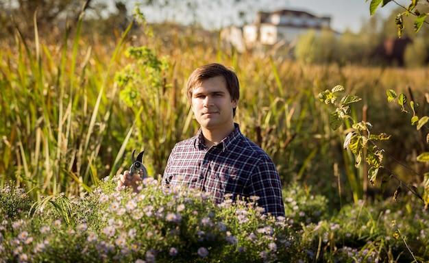 Retrato tonificado de homem trabalhando no jardim e cortando flores