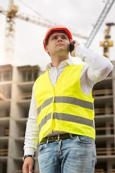 Retrato tonificado de jovem engenheiro de construção falando por telefone no canteiro de obras