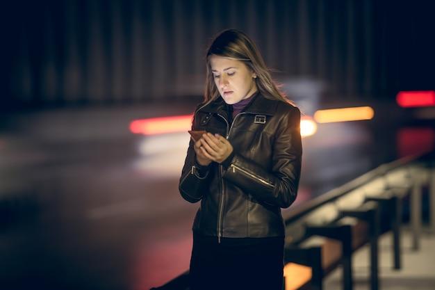 Retrato tonificado de mulher com smartphone à noite na rodovia Foto Premium