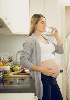 Retrato tonificado de mulher grávida bebendo água na cozinha