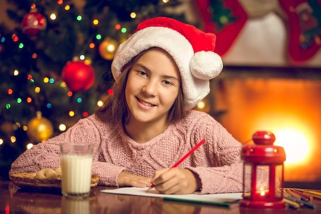 Retrato tonificado de uma garota sorridente escrevendo uma carta para o papai noel