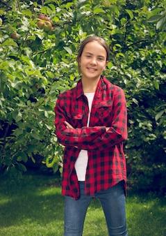 Retrato tonificado de uma jovem sorridente e feliz com camisa quadriculada, posando no pomar