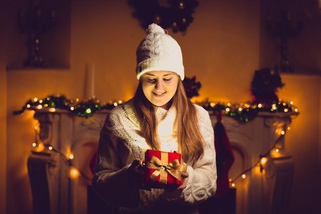 Retrato tonificado de uma mulher fofa de suéter e chapéu segurando uma caixa de presente brilhante na sala de natal decorada