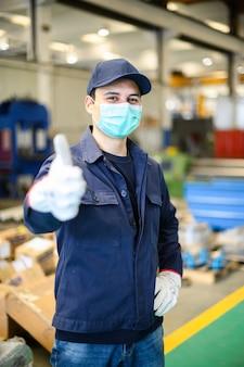Retrato, trabalhador, planta industrial, máscara, desistir, polegares, conceito, coronavirus