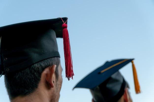 Retrato traseiro de graduado vestindo um chapéu negro.