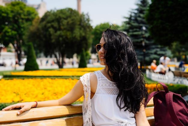 Retrato uma linda garota descansa em um banco em istambul, aproveitando o sol. flores ao fundo