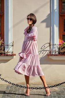 Retrato urbano ao ar livre da jovem menina elegante bonita no vestido rosa oversized