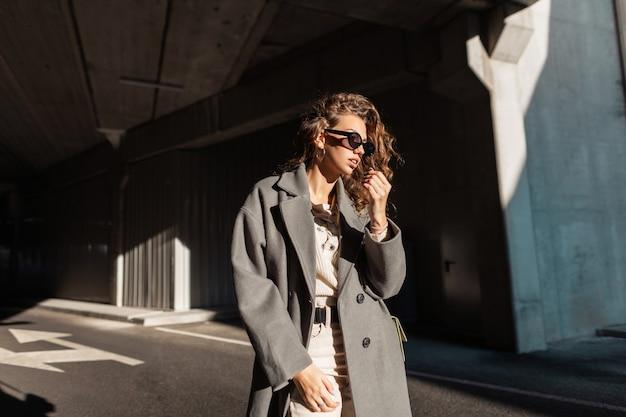 Retrato urbano da moda de mulher elegante e muito encaracolada com óculos de sol em um casaco longo casual vintage caminha na rua