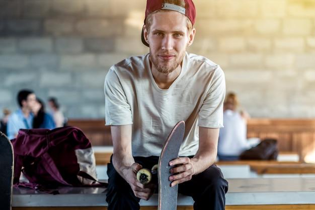 Retrato urbano da rua do jovem hippie sente-se no banco com o skate ao ar livre.