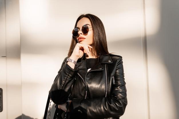Retrato urbano de uma jovem elegante com óculos de sol redondos vintage em uma jaqueta de couro da moda perto de um muro na rua na luz do sol