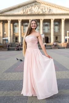 Retrato urbano de uma modelo jovem, esguia e linda em um vestido rosa