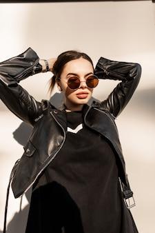 Retrato urbano elegante de uma linda mulher com lábios naturais e rosto bonito em uma jaqueta de couro da moda com óculos de sol redondos perto de uma parede cinza ao pôr do sol