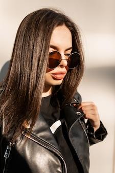 Retrato urbano fresco do modelo de mulher bonita com rosto bonito em roupas pretas da moda com uma jaqueta de couro e óculos de sol redondos retrô na cidade ao pôr do sol