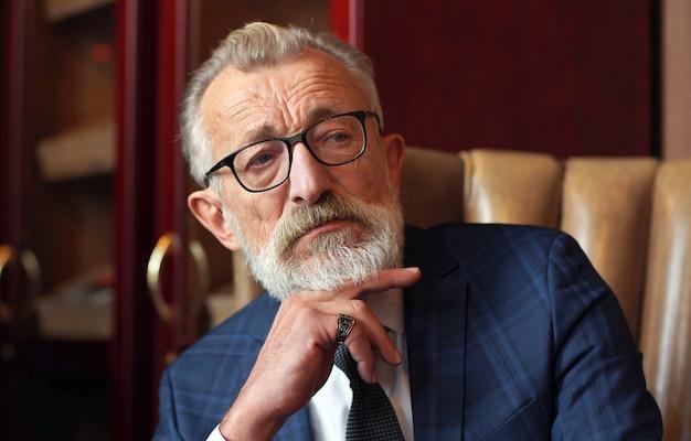 Retrato, velho, homem, elegante, roupas, óculos, sentando, couro, cadeira, dentro, sala, close-up