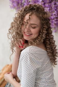 Retrato vertical closeup de menina suavemente encaracolado com sorriso largo no fundo floral - imagem