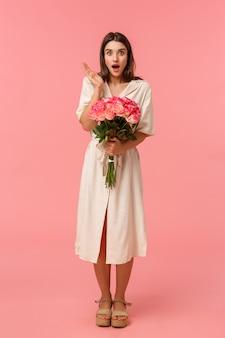 Retrato vertical completo garota muito surpresa recebe presente inesperado, tem entrega segurando flores, ofegante boca aberta espantado e olhando sem palavras com expressão atordoada, rosa
