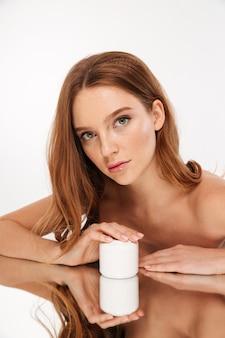 Retrato vertical da beleza da mulher ruiva com cabelo comprido reclina na mesa de espelho, segurando o frasco de creme corporal e olhando