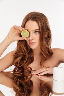 Retrato vertical da beleza da mulher ruiva com cabelos longos, sentado junto à mesa de espelho com creme corporal e frutas cítricas
