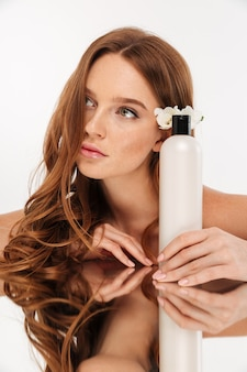 Retrato vertical da beleza da mulher ruiva com flor no cabelo, sentado junto à mesa de espelho com uma garrafa de loção enquanto olhando para longe
