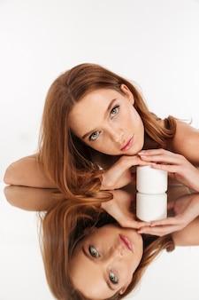 Retrato vertical da beleza da mulher sorridente de gengibre com cabelos longos, posando na mesa de espelho com uma garrafa de creme para o corpo enquanto olha
