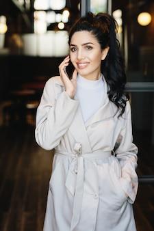Retrato vertical da elegante empresária morena de jaleco branco, comunicando-se por telefone celular