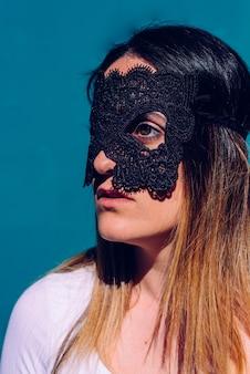 Retrato vertical da jovem mulher atrativa com máscara preta em sua cara, gesto sério, para manter sua privacidade.