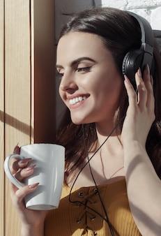 Retrato vertical da menina sorridente, ouvindo música e tomando café no peitoril da janela