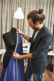 Retrato vertical de adulto bonito caucasiano masculino estilista com penteado elegante com roupa elegante em seu estúdio, trabalhando no vestido novo para a coleção de roupas de inverno