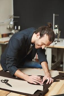 Retrato vertical de alegre atraente caucasiano masculino maduro estilista com penteado elegante terno preto, trabalhando na nova coleção de roupas para desfile de moda, cortando as peças do vestido