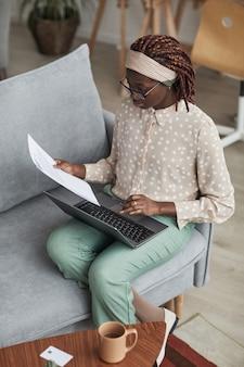 Retrato vertical de alto ângulo de uma jovem afro-americana usando óculos e usando laptop enquanto está sentada no sofá e trabalhando em casa