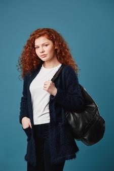 Retrato vertical de aluna bonita com cabelo vermelho ondulado, segurando a mão no bolso, segurando a bolsa preta, tendo um olhar feliz e confiante.