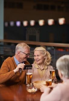 Retrato vertical de casal sênior moderno tirando foto de selfie enquanto bebe cerveja no bar e se diverte com os amigos, copie o espaço