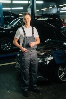 Retrato vertical de comprimento total de sorrindo bonito jovem mecânico masculino vestindo uniforme, segurando specia.