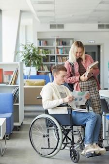Retrato vertical de corpo inteiro de alegre estudante deficiente conversando com uma jovem na biblioteca da faculdade