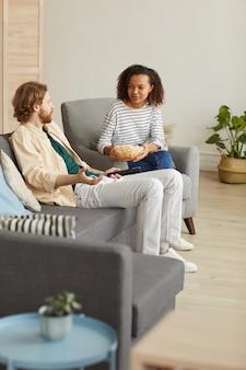 Retrato vertical de corpo inteiro de casal mestiço moderno curtindo o tempo em casa, assistindo tv enquanto relaxa no sofá aconchegante e come pipoca