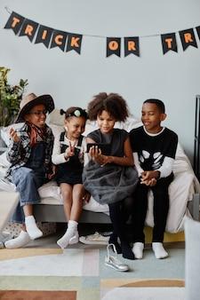 Retrato vertical de corpo inteiro de crianças vestindo fantasias de halloween dentro de casa sob enfeites e guirlandas