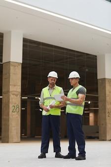 Retrato vertical de corpo inteiro de dois empreiteiros de construção usando tablet digital enquanto estão em um canteiro de obras