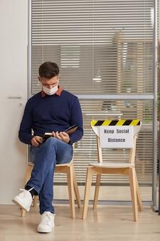 Retrato vertical de corpo inteiro de homem maduro usando máscara e lendo um livro enquanto espera na fila no escritório com a placa keep social distance, copie o espaço