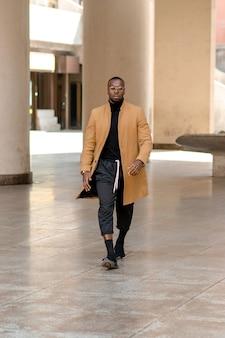 Retrato vertical de corpo inteiro de homem negro elegante andando na cidade. estilo de vida urbano.
