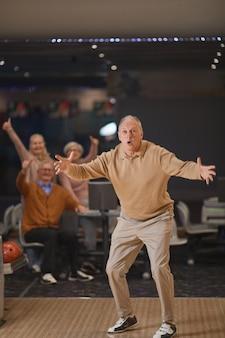 Retrato vertical de corpo inteiro de homem sênior animado jogando boliche e comemorando vitória ou greve com um grupo de amigos no fundo
