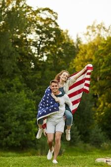 Retrato vertical de corpo inteiro de jovem casal despreocupado correndo em gramado verde com uma bandeira americana acenando
